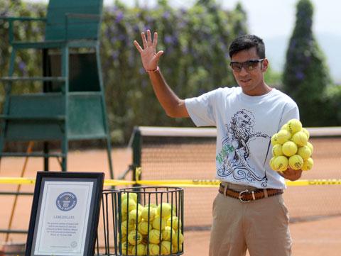 Najwięcej piłek tenisowych trzymanych w dłoni