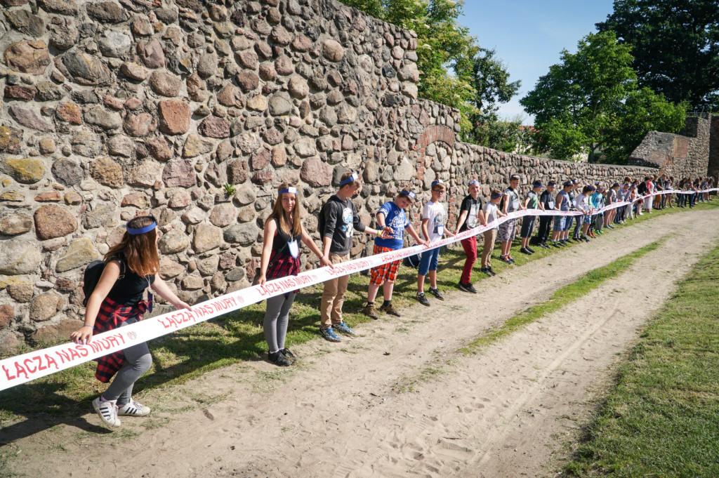 Najwięcej osób trzymających wstęgę wzdłuż murów